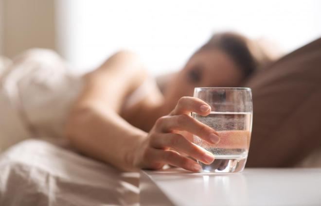 woman-in-bed-reaching-for-glass-of-water-to-drink-before-going-to-sleep